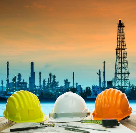 industrial landscape: Casco di sicurezza sul ingegnere tavolo di lavoro contro il bel raffineria di petrolio in settore immobiliare