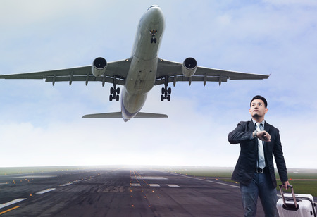 runways: young business man standing in airport runways with belonging luggage lookin to time watch and sky above , jet plane take off from runways use for traveling ,journey on busy time Stock Photo