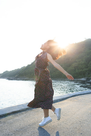 side lighting: beautiful young woman jumping at sea side against sun lighting over sky