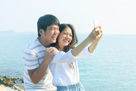 life style: young man and woman take a photo by smart phone at sea side use for new people life style and technology activities