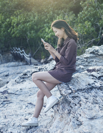 life style: young beautiful woman connecting people by smart phone on sea side location with happy face use for digital communication technology and modern life style theme