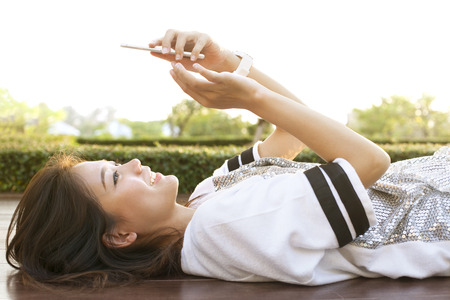 young beautiful woman lying on home terrace and playing smart phone in hand use for people and modern technology to connecting in social media and digital activities life style