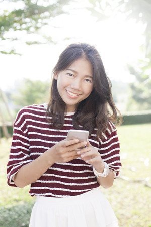 life style: portrait of beautiful young woman and smart phone in hand smiling to camera use for modern activities life style and hi-technology of younger women