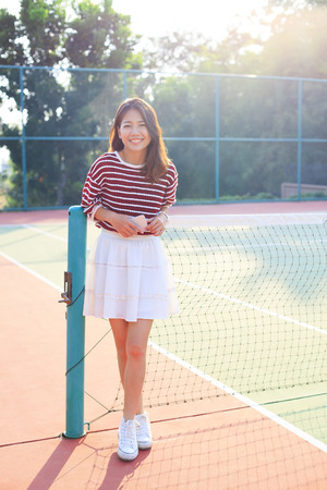 tennis skirt: portrait of beautiful young asian woman waearing white clothes skirt in tennis course with happy face