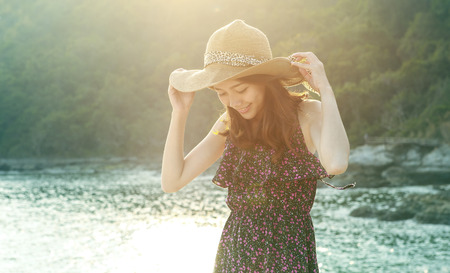 portrait of young beautiful woman wearing long dress and wide straw hat smiling at sea side location  use for modern life fashion and people activities on vacation photo