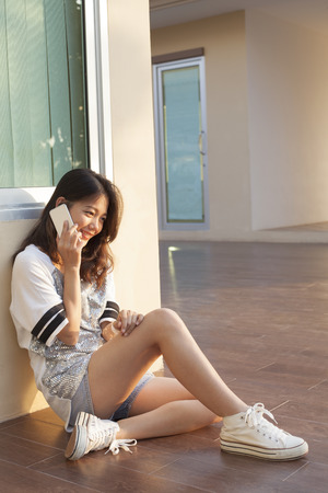thai teen: portrait of beautiful young and teen woman talking mobile phone with smiling face in home outdoor