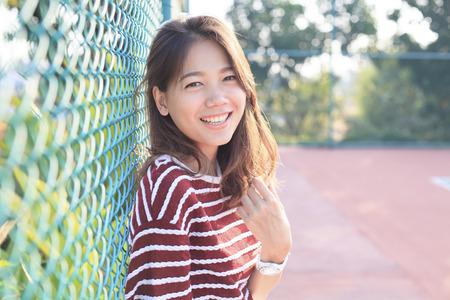caras felices: retrato de la hermosa mujer joven con dientes sonriendo con cara feliz con alta luz de la tarde en el uso del pelo para la gente felicidad y confianza femenina