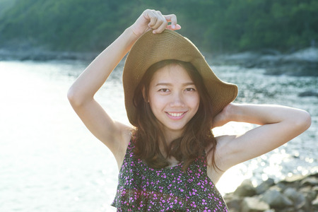 teen girl smile face: portrait face of beautiful woman wearing wide straw hat standing at sea side eyes looking to camera use for people on vacation and natural beauty of young and teen
