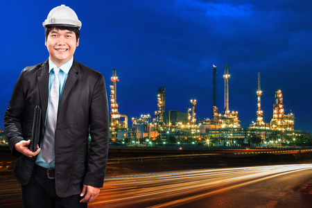 power industry: engineering man and oil refinery plant against beautiful blue dusky sky and vehicle lighting on asphalt road use as land transport and oil power industry topic background