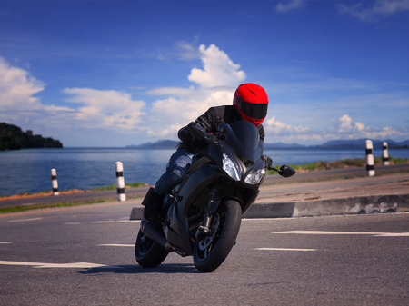 motorcycle: young biker man riding motorcycle on asphalt road against beautiful sea water background Stock Photo