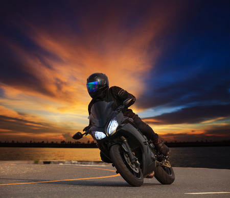 motors: young man riding big bike motorcycle leaning curve on asphalt highways road against beautiful dusky sky use as people adventure sport leisure theme Stock Photo