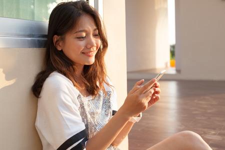 라인 연결 기술에 대한 이야기 채팅 및 인터넷 집 야외 사용에 얼굴에 미소와 함께 휴대 전화를 찾고 아름다운 젊은 십대 여자의 초상화 스톡 콘텐츠