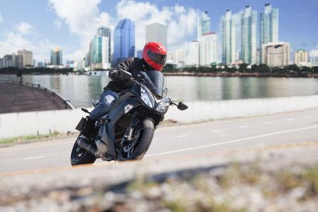 jonge man rijden op grote fiets motorfiets op de stadsweg tegen de stedelijke en de stad gebouw scene achtergrond gebruiken voor mensen en gemak voertuig te reizen in de stad Stockfoto
