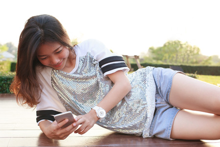 out door: portrait of young beautiful woman lying and reading text on smart phone  Stock Photo
