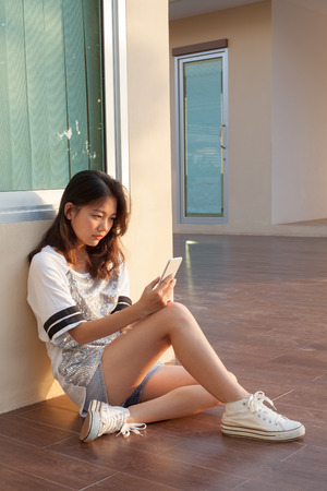 portrait of teen woman with serious face looking and reading message on mobile phone by unhappy face use for people and life problem photo