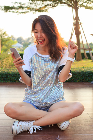 portrait of young woman watching to mobile phone screen with surprising and happiness face photo