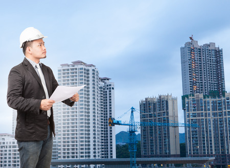 property development: engineering man wearing western suit and safety helmet with building plan document working on high scrapper building construction site