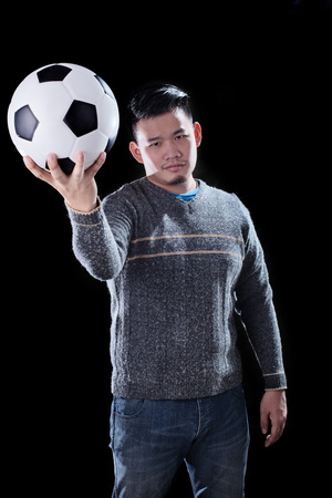 mania: young asian man and soccer ball on dark background use for football mania