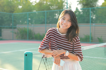 portrait of beautiful young asian woman wearing white clothes skirt in tennis course with happy face photo