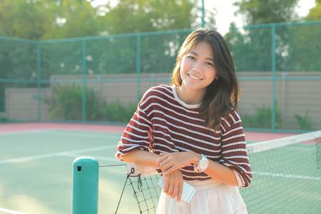 falda corta: Retrato de una hermosa mujer asiática joven con atuendos de la falda blanca en pista de tenis con la cara feliz