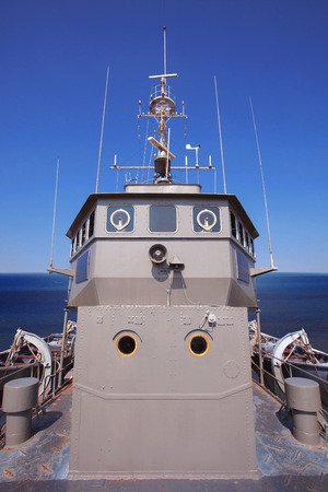ship captain: front view of military ship bridge control room against clear blue sea and sky