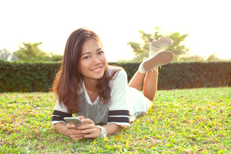 communicated: portrait of beautiful young woman lying on green grass field and holding modern smart phone in hand and smiling with happy face emotion
