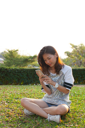 communicated: woman sitting on grass field and looking to smart phone