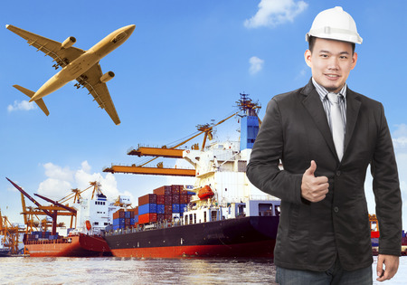 export import: working man and commercial ship on port and air cargo plane flying above use for water and air transport,logistic import export industry Stock Photo