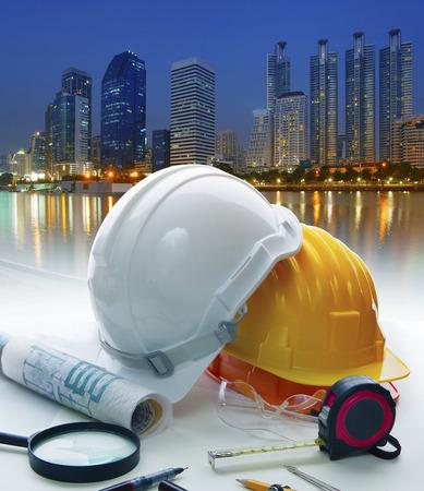 ingenieur werktafel met veiligheidshelm en het schrijven van apparatuur tegen mooie verlichting van het gebouw in stedelijke scène Stockfoto