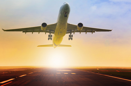 plane landing: passenger jet plane take off fron airport runway with beautiful light of sun rising behind