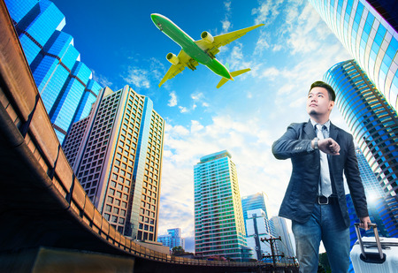 young business man and belonging luggage standing against building urban scene looking to sky with passenger jet plane flying above use for people in traveling theme photo
