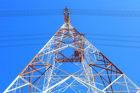power line tower: symmetry of high voltage electric power line tower metal structure against clear blue sky