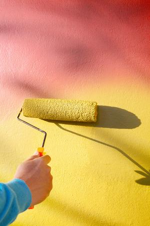 reengineering: hand painting yellow wall by roller painter brush