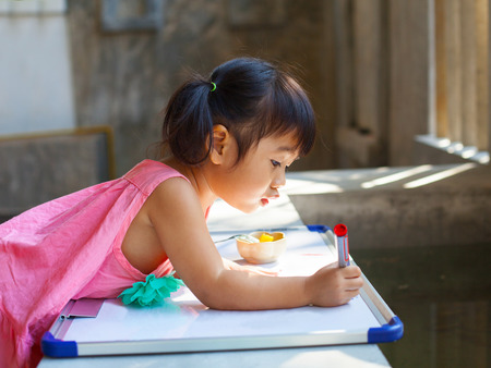 meditation room: lovely kid practice for writing on white broad before class learning in pre kindergarten