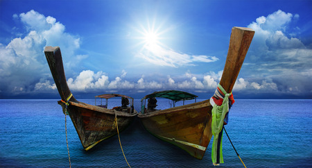 southern thailand: thai andaman long tailed boat southern of thailand on sea beach with beautiful sun shining over sky
