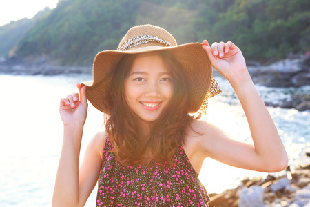 face shot: portrait face of beautiful woman wearing wide straw hat standing at sea side