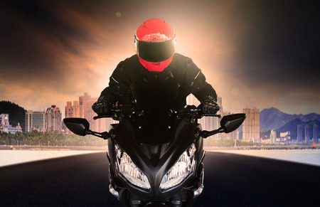 close up rider man wearing safety suit and anti knock helmet riding big bike motorcycle on asphalt street against urban and sky scrapper building use for people activities and city life transportation theme