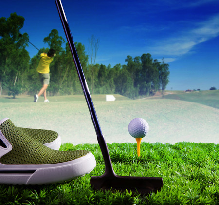 individual sport: golf ball and putter on green grass of course against young man driving golf in field use for individual outdoor sport