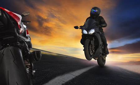 motors: young man riding motorcycle on asphalt highways road with professional extreme biking skill use for sport racing and people vacation activities Stock Photo
