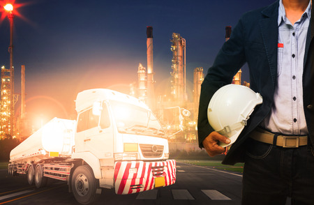 land transport: engineer holding hard hat standing against beautiful lighting of oil refinery in heavy petrochemical industry and big oil container truck use for petroleum industrial and land transport business Stock Photo