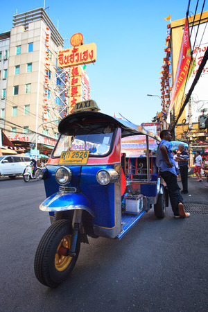 gold road: THAILAND,BANGKOK - FEB 24 :Tuk Tuk thailand vehicle symbol parking in Yaowarat Road,the main street in Chinatown, once of Bangkok landmark and important street for sale and buy gold in bangkok on february 24, 2015 in China town, Bangkok Thailand Editorial