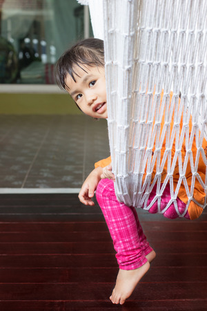 warm home: face of children sitting in clothes cradle and smiling use for family relaxing time and warm home