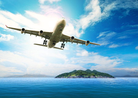 fly: passenger plane flying over beautiful blue ocean and island in purity destination sea beach use for summer holiday vacation treveling
