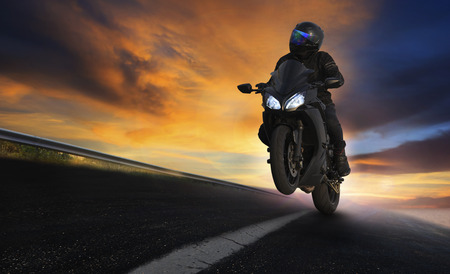 young man riding motorcycle on asphalt highways road with professional extreme biking skill use for sport racing and people vacation activities Stock Photo