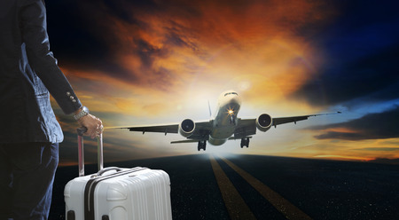 runways: young business man and luggage suitcase standing with passenger plane take off from runways against beautiful dusky sky with copy space use for air transport ,journey and traveling industry business
