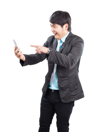 communicated: portrait of young asian business man pointing hand to smart phone with happiness emotion face isolated on white background Stock Photo