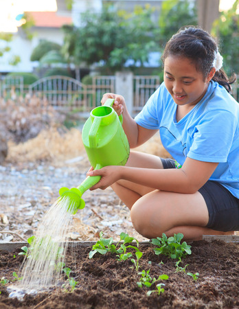 girl watering vegetable plant in home garden field family relaxing time photo