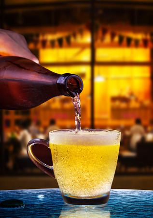 lager beer drain from bottle to glass on table with beautiful lighting of snack bar use for alcohol drinking beverage  in adult pub ,bar and restaurant photo