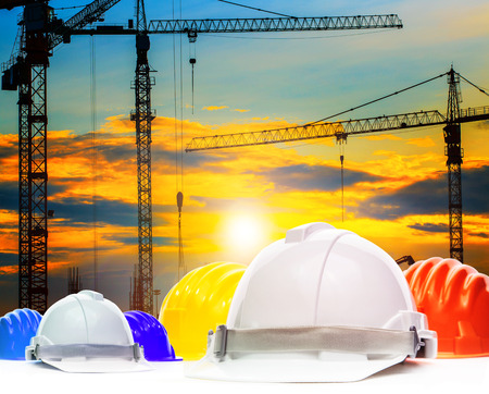 safety helmet and structure of high crane in construction site against beautiful evening sky use for engineering and architecture in working field and buiding construction plant background,backdrop photo