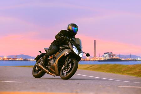 jinete: hombre joven que monta la motocicleta sport touring en las carreteras de asfalto contra hermoso iluminaci�n de uso escena industria urbana como la gente moderna forma de vida y las actividades de vacaciones Foto de archivo